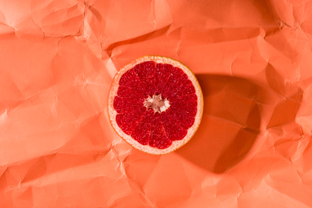 grapefruit half on crumpled paper textured coral surface, color of 2019 concept