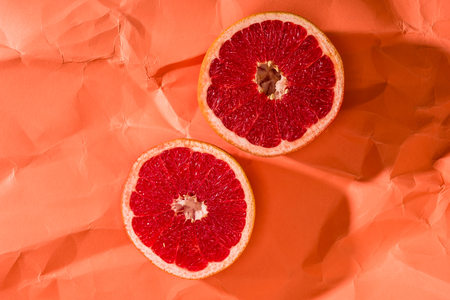 grapefruit halves on crumpled paper textured coral surface, color of 2019 concept