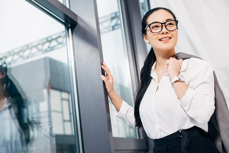 pretty businesswoman with jacket over shoulder standing by window in office