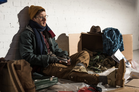 homeless man sitting by brick wall surrounded by rubbish Stock Photo