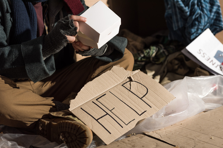 partial view oh homeless man in fingerless gloves sitting near cardboard card with