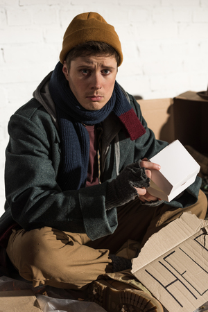 sad homeless man sitting with cardboard card with help lettering and holding white paper box Stock Photo