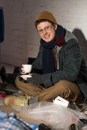smiling homeless man in glasses drinking coffee while sitting on rubbish dump