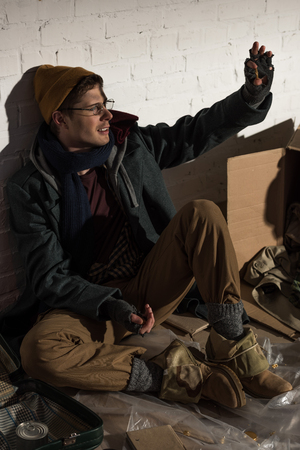 homeless beggar man sitting by brick wall and waving hand Stock Photo