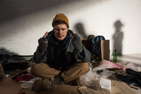 homeless man showing middle fingers while sitting surrounded by rubbish