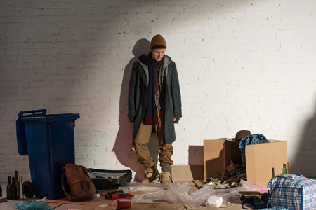 homeless man standing by white brick wall on rubbish dump