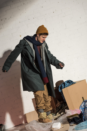 angry homeless man standing above cardboard box with garbage Banco de Imagens