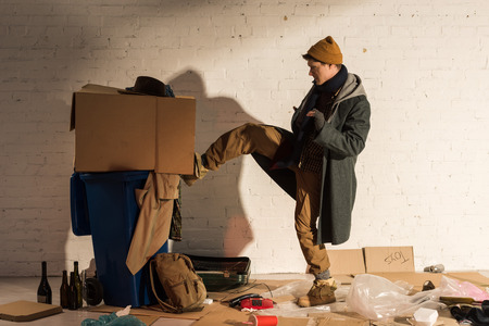 angry homeless man kicking trash container with cardboard box