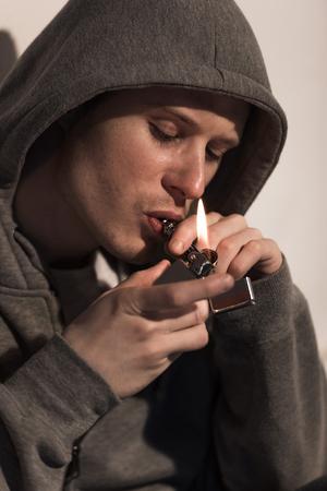 close up of man in hood lightening smoking pipe