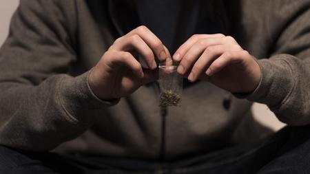 selective focus of junkie man opening pack with marijuana