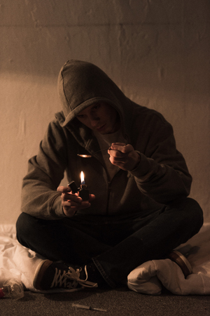 junkie man sitting in dark room and heating spoon with heroin on lighter
