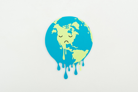 melting paper cut globe with sad face expression on grey background, global warming concept Stock Photo