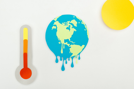 paper cut sun and melting earth, and thermometer with high temperature indication on scale on grey background, global warming concept