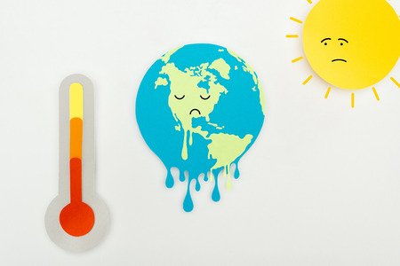 paper cut sun and melting earth with sad faces expression, and thermometer with high temperature indication on scale on grey background, global warming concept