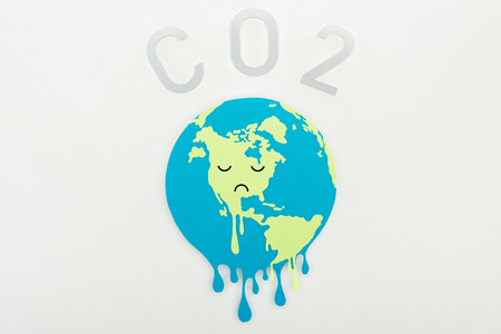 paper cut melting earth with sad face expression, and co2 lettering on grey background, global warming concept Banco de Imagens