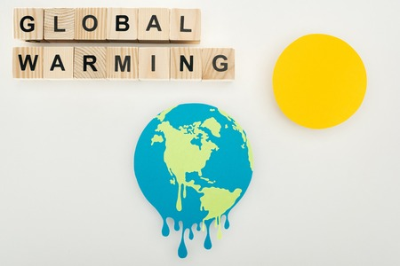 paper cut melting earth and sun, and wooden cubes with global warming lettering on grey background