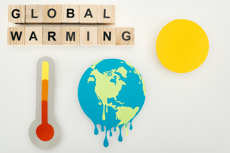 paper cut melting earth and sun, thermometer with high temperature indication on scale, and wooden cubes with global warming lettering on grey background