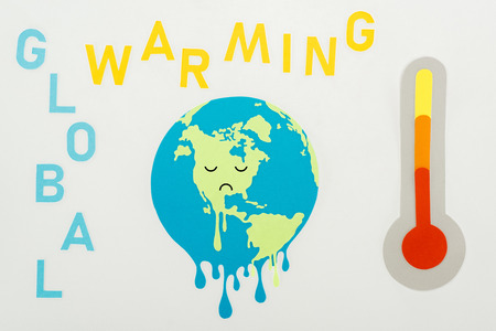 paper cut melting globe with sad face expression, global warming lettering, and thermometer with high temperature indication on scale on grey background Stock Photo