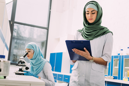 concentrated female muslim scientists using microscope and writing in clipboard during experiment in chemical laboratory Imagens