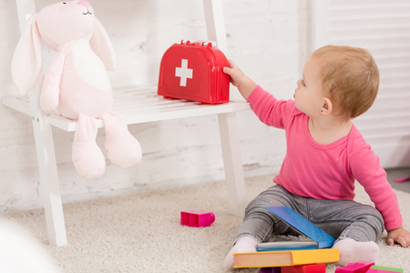 adorable kid taking first aid kit in children room Banque d'images - 117878075