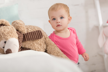 adorable kid standing near teddy bear and looking up in children room Stock Photo