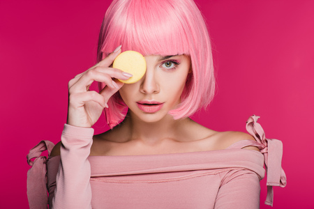 young fashionable woman in pink wig posing with macaron isolated on pink 写真素材