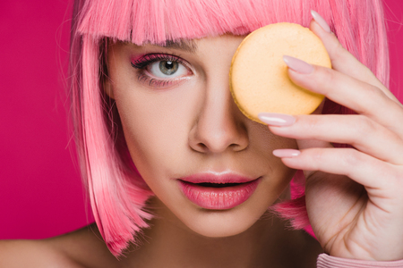 attractive girl in pink wig posing with yellow macaron isolated on pink