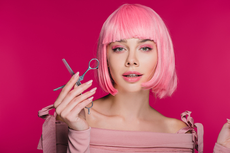 beautiful stylish girl in pink wig holding scissors isolated on pink Фото со стока - 117865922