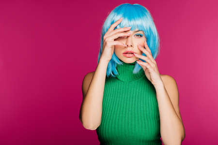 attractive fashionable girl posing in blue wig, isolated on pink