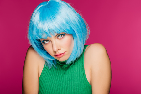 charming young woman posing in blue wig, isolated on pink