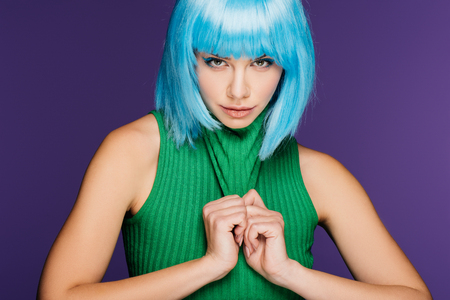 attractive girl posing in blue wig and green turtleneck, isolated on purple