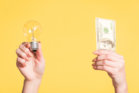 cropped view of female hands holding led lamp and hundred dollar banknote in hands isolated on yellow, energy efficiency concept Stock Photo