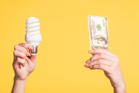 cropped view of female hands holding fluorescent lamp and hundred dollar banknote in hands isolated on yellow, energy efficiency concept