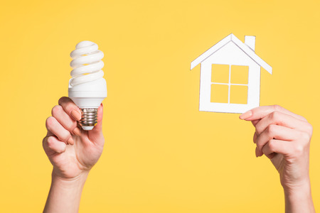 cropped view of female hands holding paper house and fluorescent lamp in hands isolated on yellow, energy efficiency at home concept