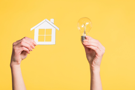 cropped view of female hands holding paper house and led lamp in hands isolated on yellow, energy efficiency at home concept