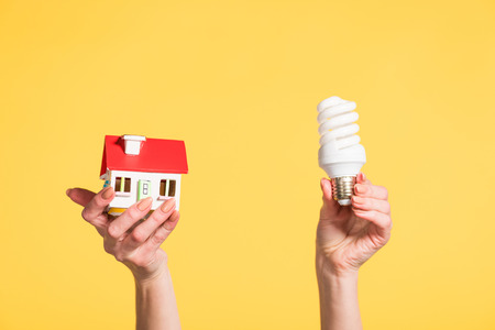 cropped view of woman holding fluorescent lamp and house model in hands isolated on yellow, energy efficiency at home concept Stock Photo