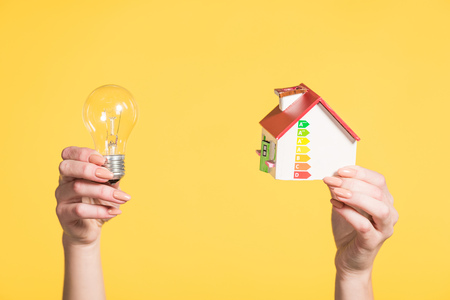 cropped view of woman holding led lamp and house model in hands isolated on yellow, energy efficiency at home concept Stock Photo
