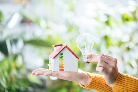 cropped view of woman holding led lamp and carton house, energy efficiency at home concept Standard-Bild