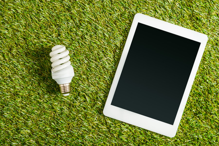top view of fluorescent lamp near digital tablet with blank screen on green grass, energy efficiency concept