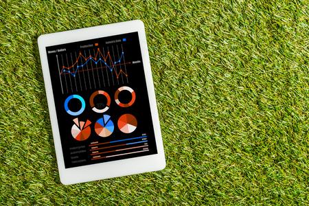 top view of digital tablet with charts and graphs on screen on green grass, energy efficiency concept