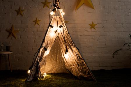 Cozy wigwam with luminous bulbs standing in dak room