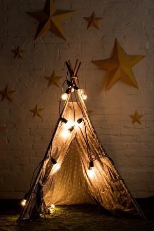 Cozy wigwam with luminous bulbs standing in dark room