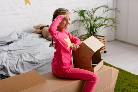 Smiling kid with helmet saluting while sitting on cardboard rocket in bedroom Stock Photo