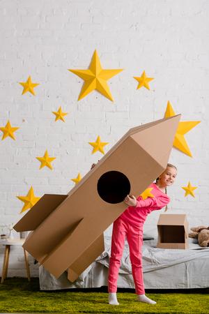 Full length view of excited kid holding big cardboard rocket in bedroom