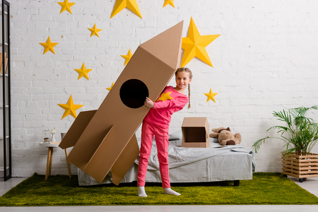 Blissful kid in pink clothes holding big cardboard rocket in bedroom