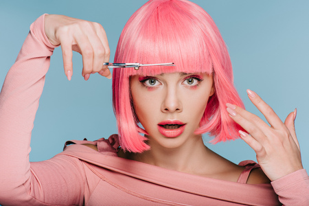 shocked stylish girl cutting pink hair with scissors isolated on blue