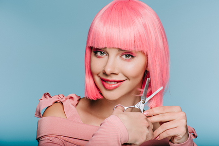 smiling fashionable girl cutting pink hair with scissors isolated on blue Фото со стока