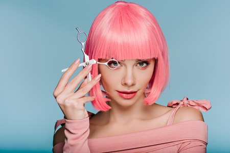 beautiful girl in pink wig posing with scissors isolated on blue Stock fotó