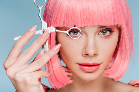 attractive sensual girl with pink hairstyle looking through scissors isolated on blue Stock fotó