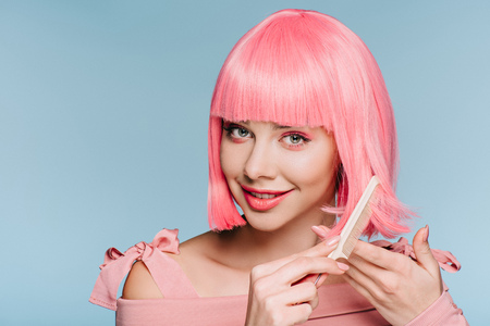 smiling girl combing pink hair isolated on blue